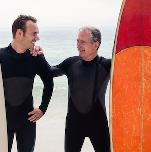 Father and son with surfboard standing on beach